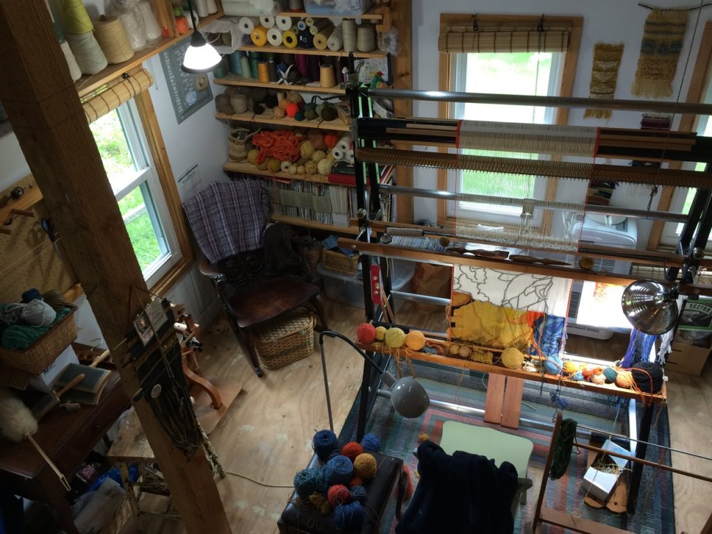 View from the loft. The yarn on the shelves is my stash of linen yarn, as well as some of the yarns I'm using for the current tapestry on the lower shelves. The yarn over the window is mostly cotton. The wool lives in plastic bins in the loft.