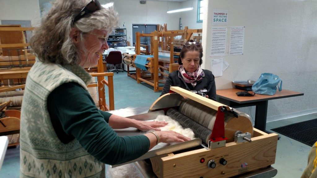 Peggy running the very first fiber into the carder. Olimpia Newman, the EVFAC Director of Development looking on