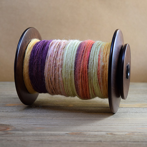 Spinning wheel bobbin filled with handspun yarn made of sheep's
